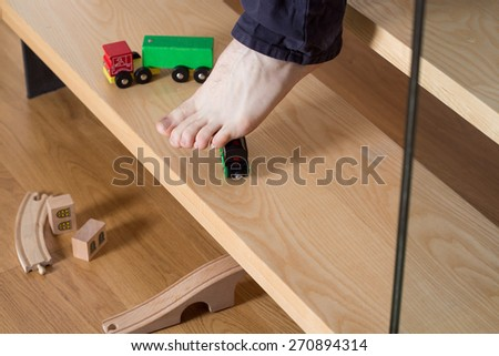 Close-up of young man's foot on stairs stepping on boy's toy - stock photo