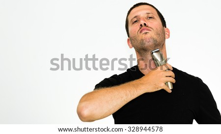 Close-up of young man shaving with electric razor wearing black tshirt