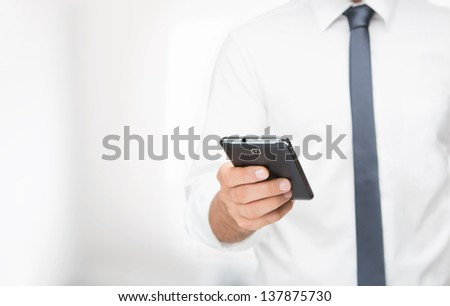 Close up of young man using smart phone at the office with copy space - stock photo