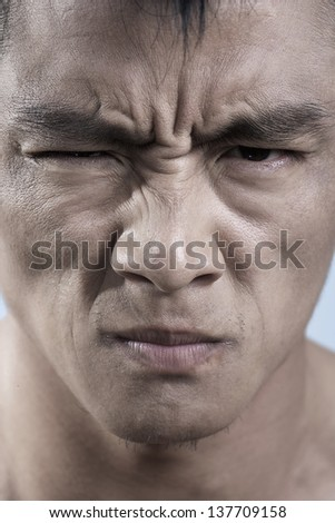 Close up of young mans face, irritated - stock photo