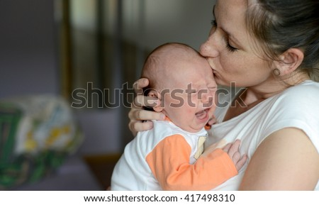 Close up of young mother holding her crying baby daughter, kissing her - stock photo