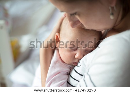 Close up of young mother holding her cute baby daughter sleeping in her arms - stock photo