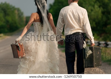 Close up of young newlywed couple holding  suitcases of cash on countryside road - stock photo
