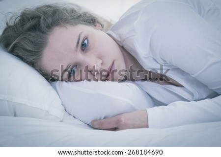 Close-up of young sad tired woman lying in bed - stock photo