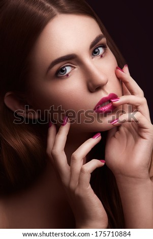 Close-up of young sexy woman with creative make-up, blonde hair and hands near her face, looking at camera