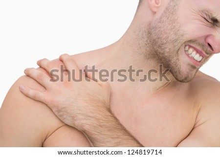 Close-up of young shirtless man with shoulder pain over white background
