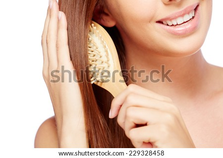Close-up of young smiling brunette brushing her long hair - stock photo