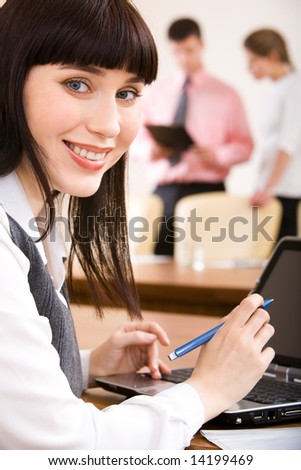 Close-up of young smiling businesswoman sitting at her workplace with laptop near by