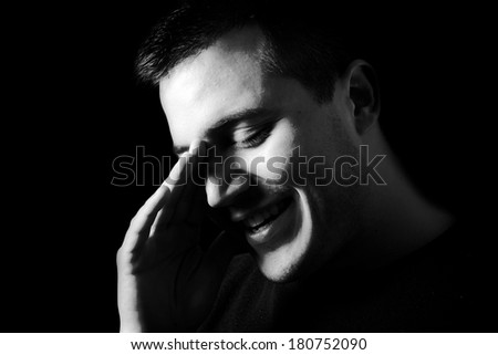 Close-up of young smiling man, low key, black and white - stock photo