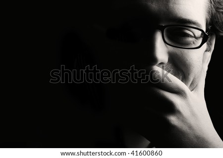 Close-up of young smiling man resting chin on palm, low key, black and white - stock photo