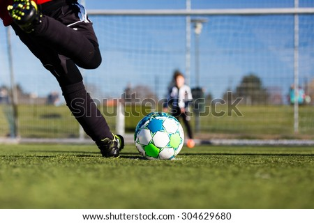 Close-up of young soccer player taking a penalty kick against a young blurred boy acting as goalie in the goal. - stock photo