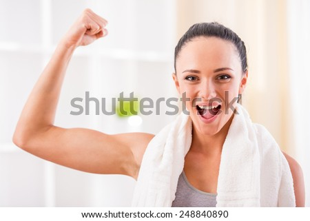 Close-up of young sporty woman flexing her biceps. - stock photo