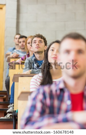 Close-up of young students sitting in a row at the college classroom - stock photo