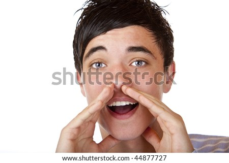 Close-up of young teenager holding hands beside his cheeks and shouts an announcement. Isolated on white.