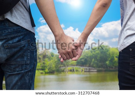 Close up of young traveler teenagers in love holding hands together over blurred of park and outdoors in bright sunny day. passion in love concept.selective focused.traveler concept. - stock photo