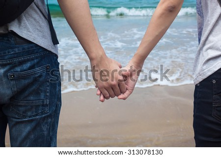 Close up of young traveler teenagers in love holding hands together over blurred of sea and beach  in bright sunny day. passion in love concept.selective focused.traveler concept. - stock photo