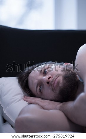 Close-up of young wake up man trying to fall asleep - stock photo