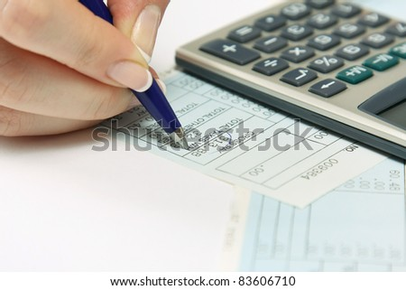 Close-up of young woman calculating bills - stock photo