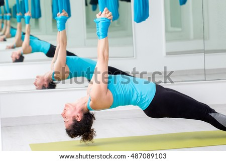 Close up of young woman doing anti gravity yoga with satin fabric.