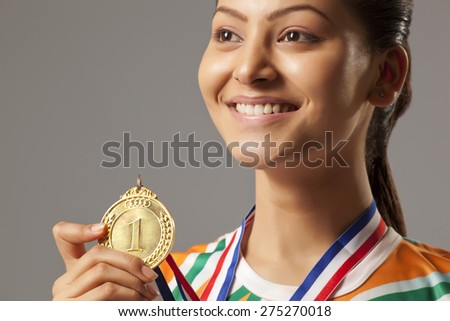 Close-up of young woman holding gold medal isolated over gray background - stock photo