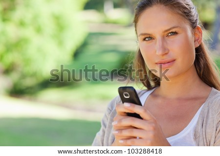 Close up of young woman holding her mobile phone in the park