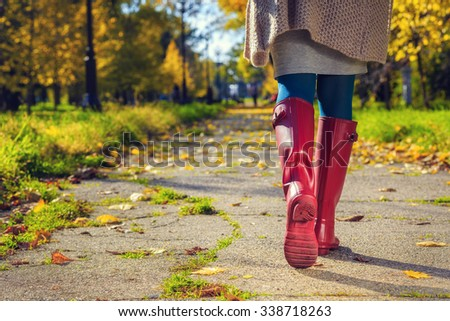 Close up of Young woman in pink rain boots walking.