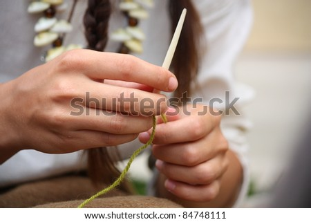 Close up of young woman knitting with bone needles - stock photo