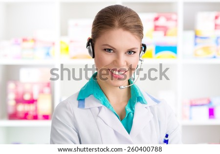 Close-up of young woman pharmacist chemist servicing customer on phone. Happy smiling female druggist wearing headset standing in drug shop. - stock photo