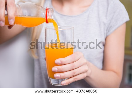 close up of young woman pouring orange juice from the bottle to the glass - stock photo