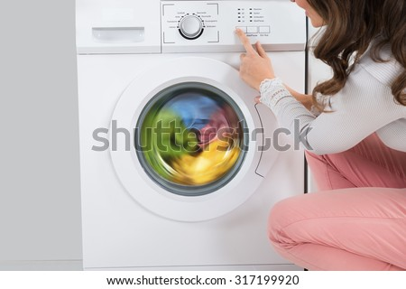 Close-up Of Young Woman Pressing Button Of Washing Machine In Kitchen - stock photo