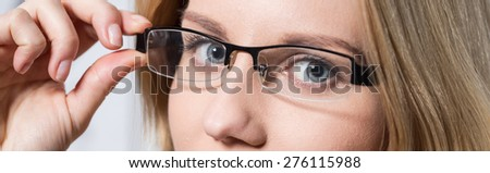 Close-up of young woman's blue eyes behind glasses - stock photo