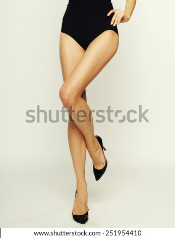 Close-up of young woman's legs in high-heeled black shoes  - stock photo