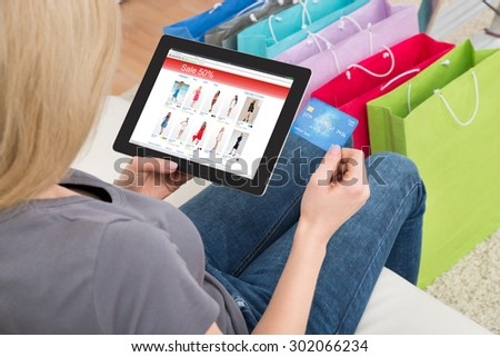 Close-up Of Young Woman Shopping Online On Digital Tablet With Credit Card - stock photo