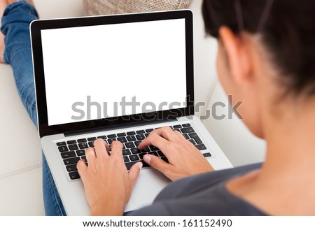Close-up Of Young Woman Using Laptop On Couch - stock photo
