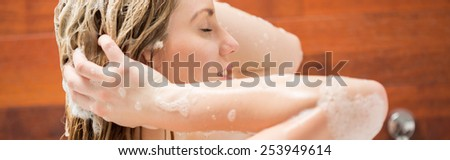 Close-up of young woman washing her hair under shower - stock photo