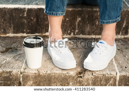 Close-up of young woman wearing blue jeans and sneakers standing near a cup of coffee outside on stone stairs - stock photo