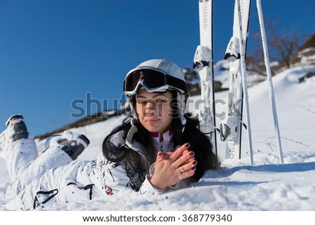 Close Up of Young Woman Wearing White Ski Suit and Lying on Stomach on Snow Covered Mountainside Next to Skis and Poles on Bright Day with Blue Sky and Warm Sunshine