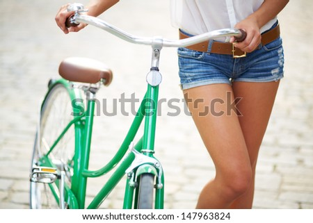 Close-up of young woman with bicycle - stock photo