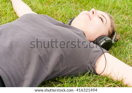 Close-up of young woman with closed eyes enjoying music during recreation time in the park - stock photo