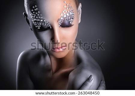 Close-up of young woman with fashion makeup with rhinestone on a dark background - stock photo