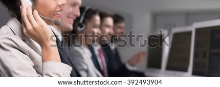 Close-up of young woman working in call center company as a telemarketer - stock photo