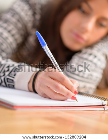 Close-up Of Young Woman Writing On Book - stock photo
