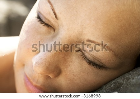 Close-up of young womans face with closed eyes.