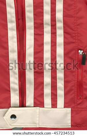 Close-up of zipper on red jacket, abstract background