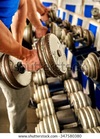 Close up og man hand working his arms with dumbbells at gym. He lifting dumbbells. - stock photo