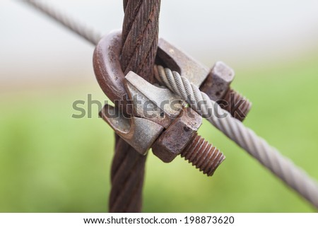 Close up old and weathered wire rope clip or clamp turnbuckle - stock photo