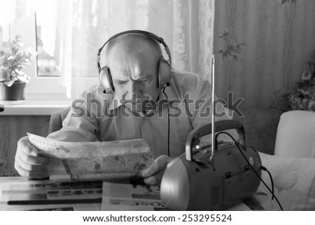 Close up Old Bald Man Reading Tabloid at the Table in Living Room While Listening Music at the Radio with Headset. Captured in Monochrome Style. - stock photo