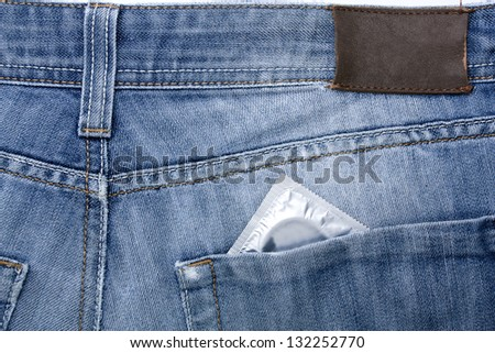 Close-up old jeans and a condom in his back pocket, symbol of safe sex - stock photo