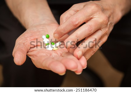 close-up old man's hands with pills, he is going to take some medicine - stock photo