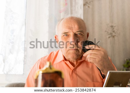 Close up Old Man Shaving his Hair on Face with Electric Razor While Looking at the Camera. - stock photo